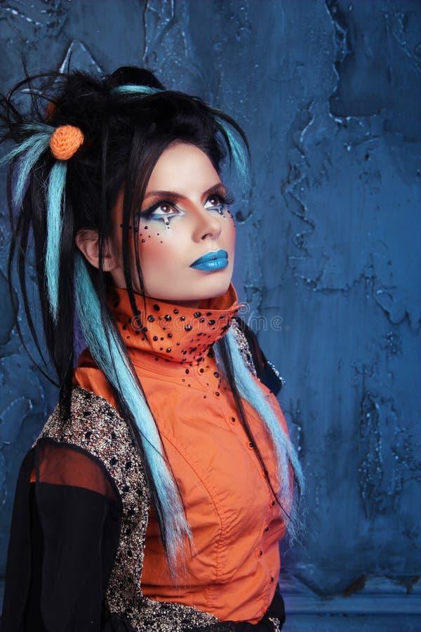 Balance a menina com bordos azuis e o penteado punk que inclinam-se contra o grun imagem de stock