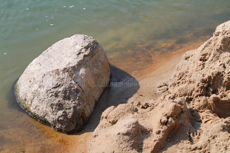 Balance in nature. Big smooth stone in warm sea water on sand beach in summer time in sunny day stock photography