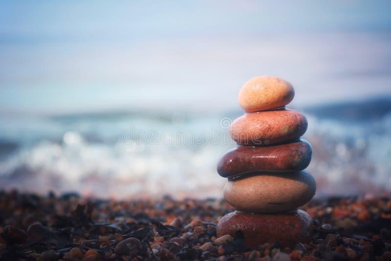 Balance o homem na praia sob um por do sol cor-de-rosa desvanecido imagem de stock