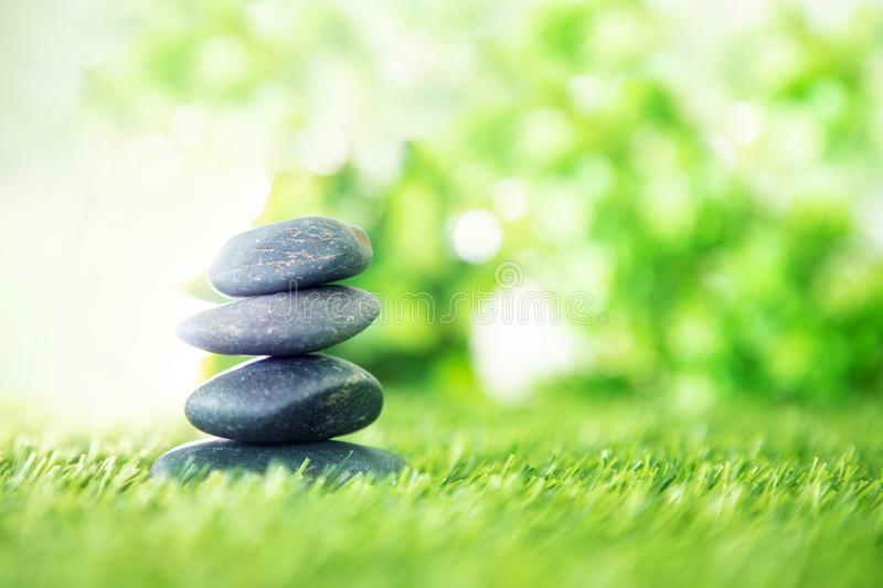 Balance with a pyramid of stone on fresh nature green grass , spa meditation or well-being with zen concept royalty free stock images