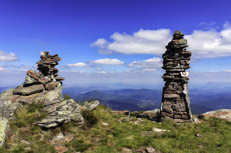 Balance of rocks and amazing blue sky on Kopren summit. Piles of rocks, amazing blue sky and mountain track signpost on Kopren summit on Old mountain, one of the royalty free stock image