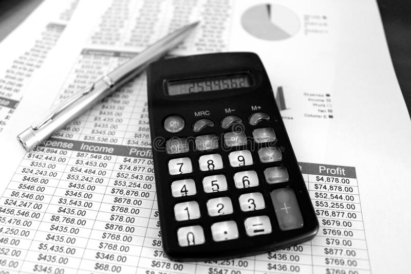 Balance Sheets Black and White. Black and white calculator over balance sheets Tables with numbers and graphs and a pen stock photo