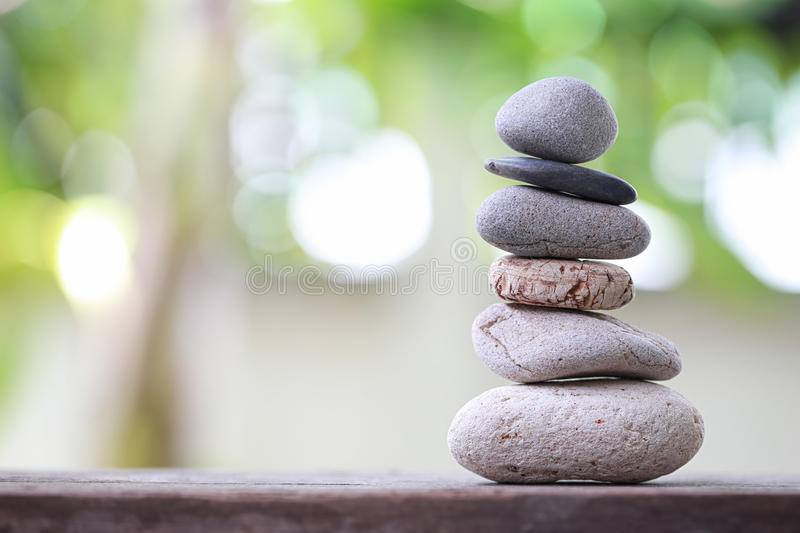 Balance Stones stacked to pyramid in the soft nature green background. stock photo