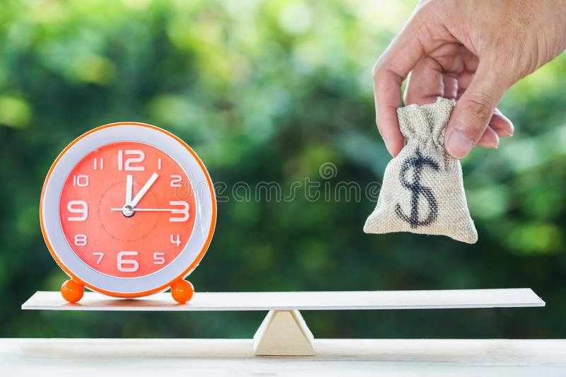 Balance time and money savings investment concept. Hand holding putting money bag over clock on scales on wood table with blurred green nature background stock photography