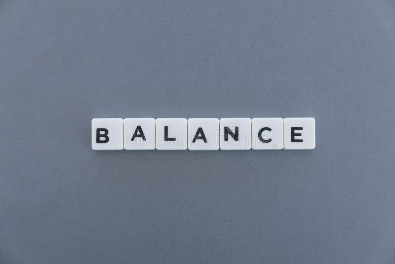 Balance word made of square letter word on grey background stock photos