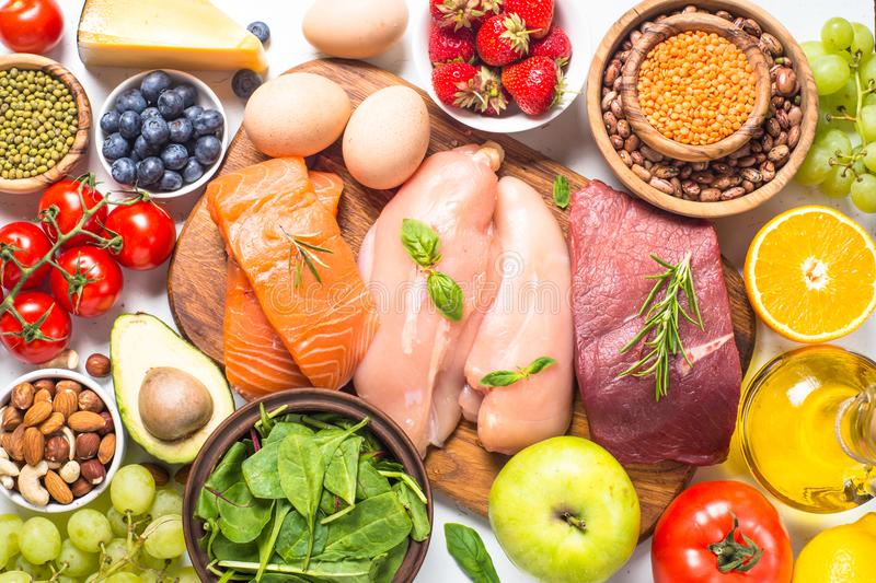 Balanced diet food background. Healthy nutrition. Ketogenic low carbs diet. Meat, fish, nuts, vegetables, oil, beans, lentils fruits and berries on white stock photos