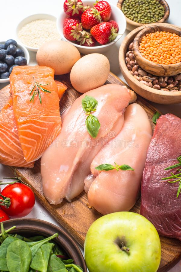 Balanced diet food background. Ketogenic low carbs diet. Meat, fish, nuts, vegetables, oil, beans, lentils fruits and berries on white background. Top view stock photo