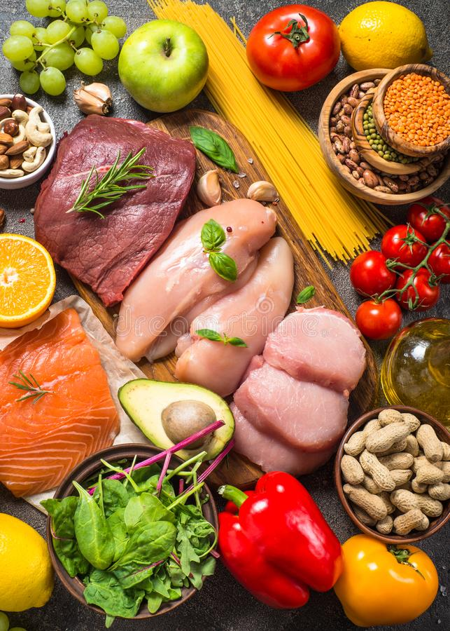 Balanced diet food background. Healthy nutrition. Ketogenic low carbs diet. Meat, fish, nuts, vegetables, oil, beans, lentils fruits and berries on dark royalty free stock photos