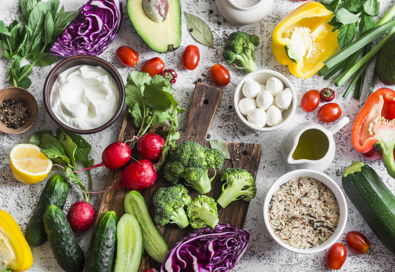 Balanced healthy diet food background in a Mediterranean style. Fresh vegetables, wild rice, fresh yogurt and goat cheese on a lig stock images