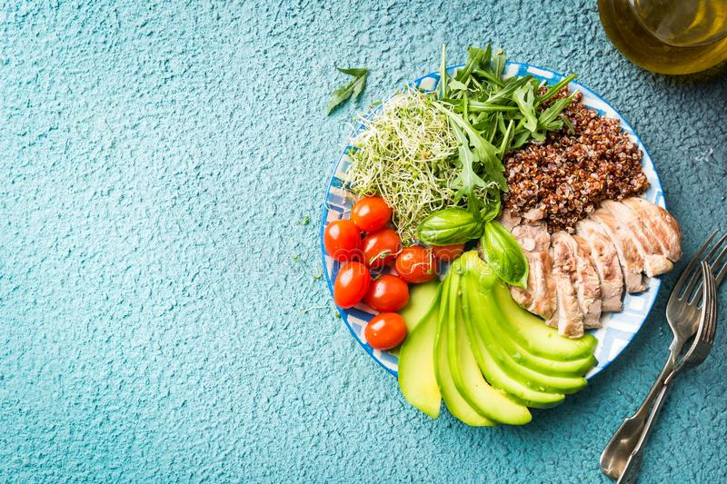 Balanced healthy food. Bowl with ingredients of balanced healthy food. Quinoa, tomatoes, chicken, avocado, and mixed greens, top view with copy space stock images