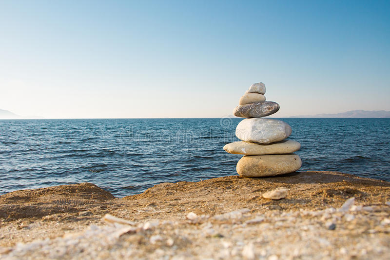 Balanced pebble tower. Symbolizing equilibrity, peace and stability resting on sandy ground with sea and vague island background stock image