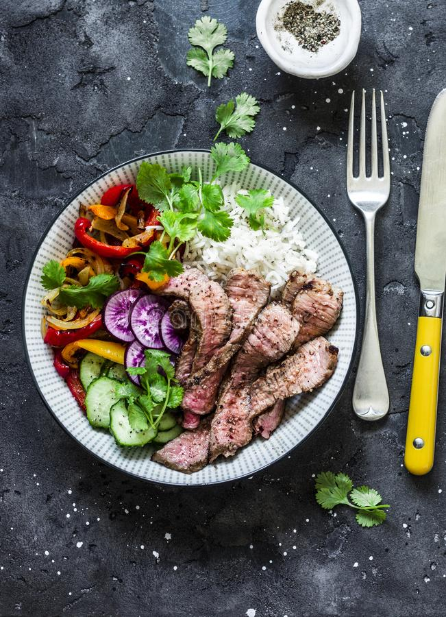 Balanced power buddha bowl - grilled beef steak, roasted and fresh vegetables, rice on a dark background, top view. Healthy diet royalty free stock images