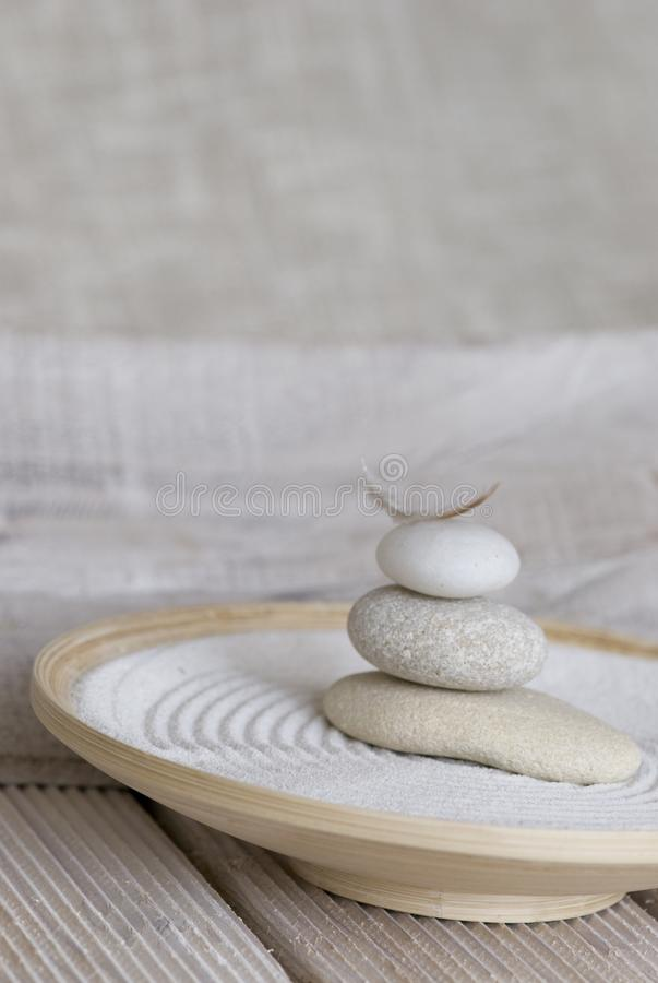 Balanced stack of smooth pebble. With little feather on top in a bamboo bowl with raked sand in the style of a Japanese garden stock photos