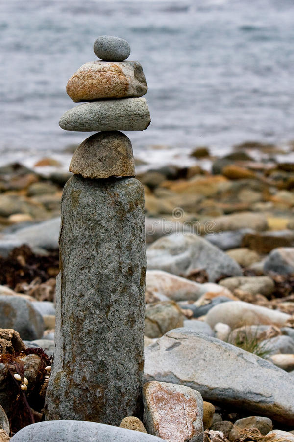 Balanced stone arrangement. A stack of pebbles and stones balanced on a rock on the shore royalty free stock image