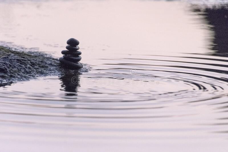Balanced stones symbols of peace. Drop water with water rings royalty free stock photos