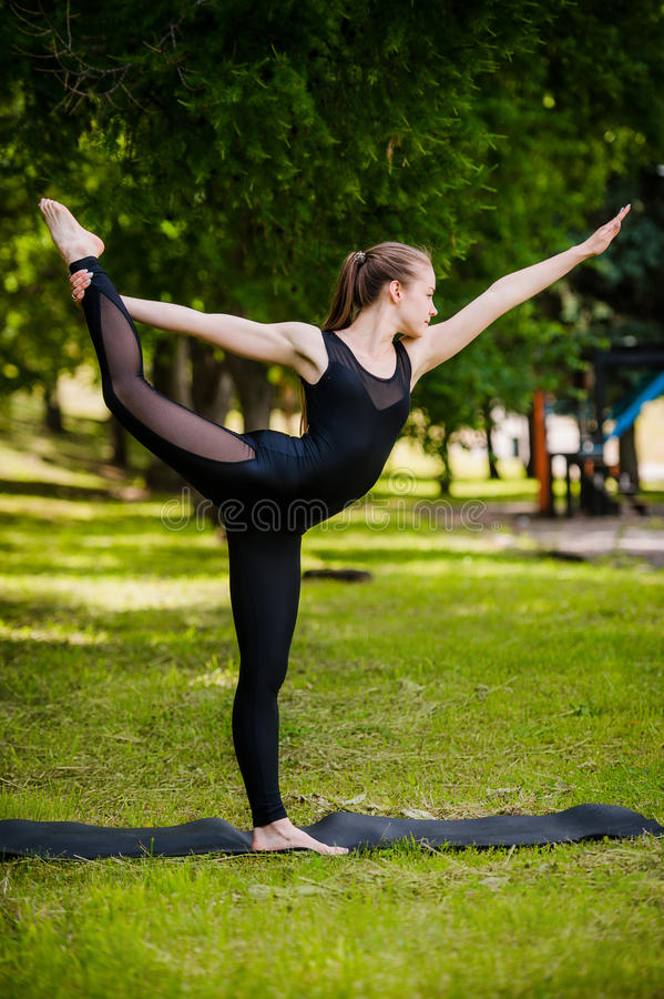 Balancenübung - junge Frau, die im Park trainiert stockbild