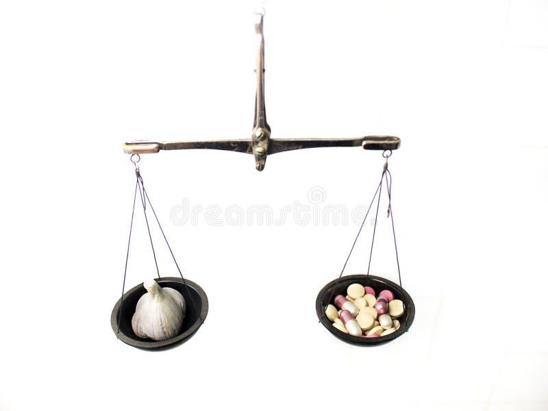 Balancenskala mit Pillen und Knoblauch stockfoto
