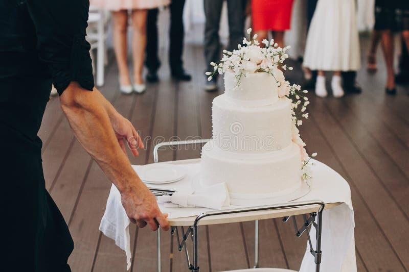 Balanceo del camarero en pastel de bodas blanco asombroso con las flores moder imágenes de archivo libres de regalías
