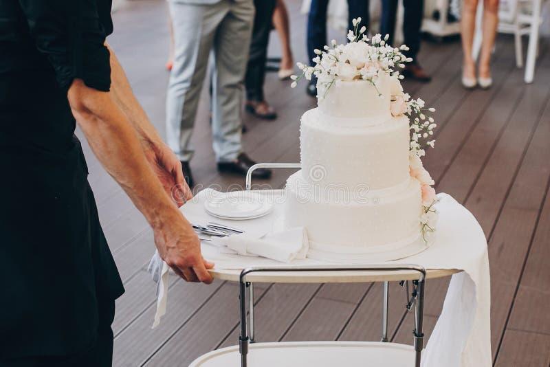 Balanceo del camarero en pastel de bodas blanco asombroso con las flores moder foto de archivo