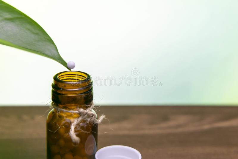 Balanceo homeopático del glóbulo de la extremidad de una hoja abajo en botella de píldoras homeopática en la superficie de madera fotografía de archivo