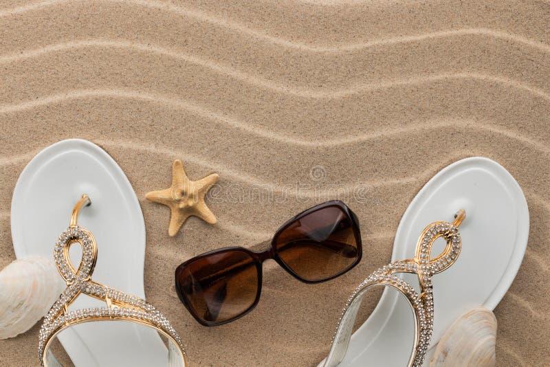 Balanceos blancos con los diamantes artificiales y sunglass, concha marina, estrella de mar en la arena ondulada foto de archivo