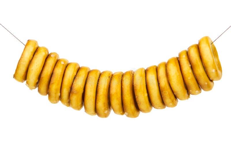 Balancer sur les anneaux de pain salés par corde d'isolement sur le blanc photo stock