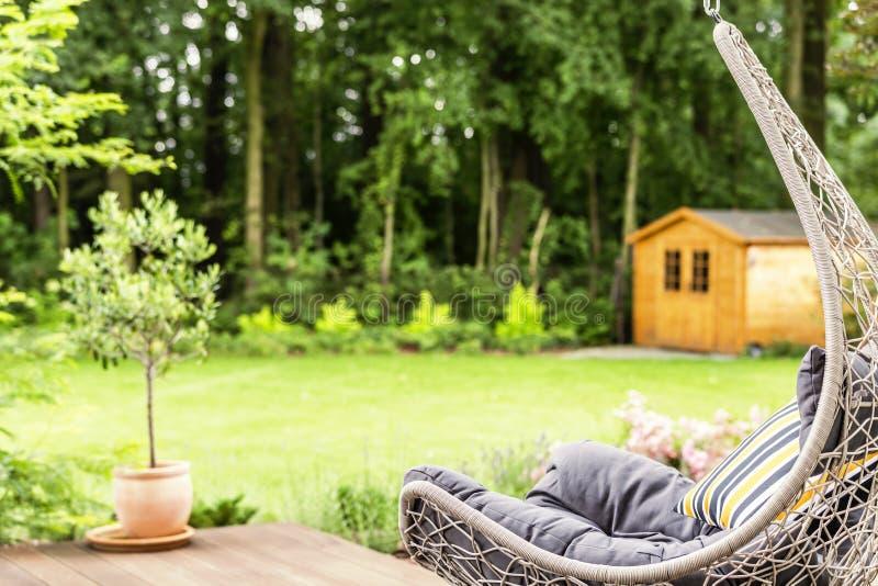Balancez la chaise avec le coussin rayé placé sur la terrasse en dehors du images stock