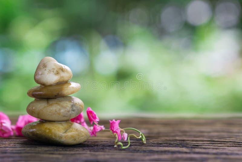 Balancieren Sie Zensteine und rosa Blume auf Holz mit grüner bokeh Rückseite lizenzfreie stockbilder
