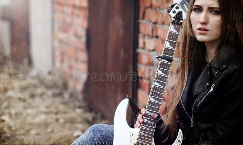 Balancim bonito da moça com guitarra elétrica Um musicia da rocha fotos de stock royalty free