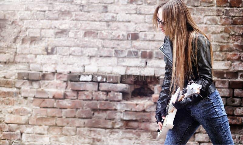Balancim bonito da moça com guitarra elétrica Um musicia da rocha fotografia de stock