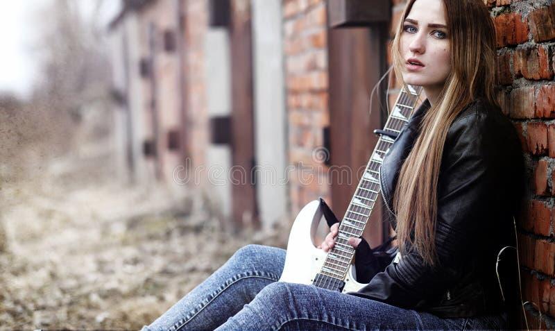 Balancim bonito da moça com guitarra elétrica Um musicia da rocha fotografia de stock royalty free