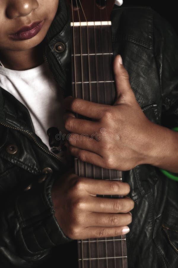 Balancim da menina no casaco de cabedal que guarda uma guitarra imagens de stock