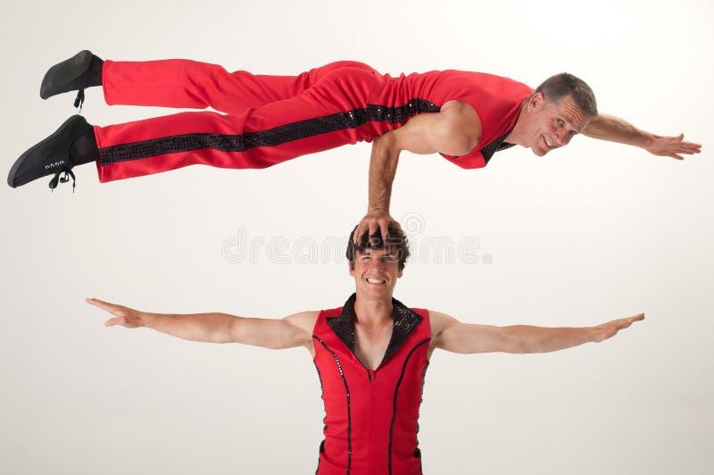 Balancing acrobat. An acrobrat balances with one arm on the head of his acrobat partner royalty free stock photos
