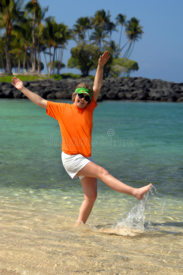 Balancing act. Adult female celebrates retirement by kicking and splashing on the beach on the Big Island of Hawaii. She is wearing a sunvisor and sunglasses royalty free stock photos