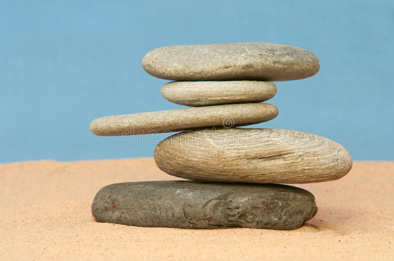 Balancing Act. Smooth waterwashed pebbles performing a balancing act on a base of sand royalty free stock images