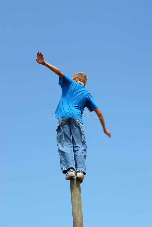 Balancing Act !. Young boy balances on wooden pole royalty free stock photos