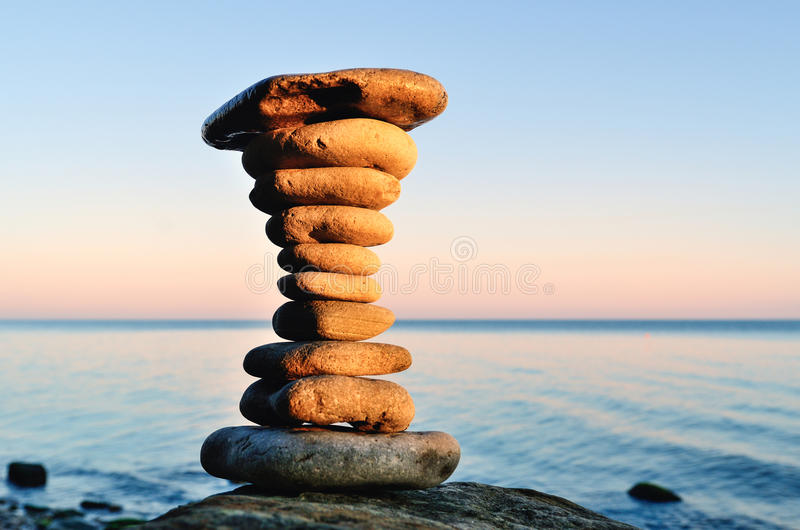 Balancing act. Balancing of stones each other on the seashore royalty free stock photo