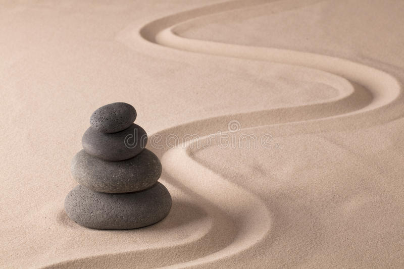 Balancing black rocks. In zen sand garden. Stone pile stacked in balance. Spa wellness or yoga background royalty free stock image