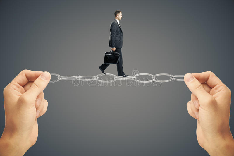 Balancing businessman. Balancing concept with businessman miniature walking on chain held by hands on dark background royalty free stock photography