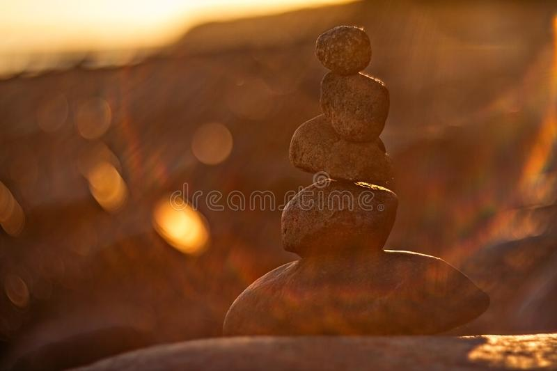 Balancing stones stacked on top of each other at sunset. Balancing five stones stacked on top of each other in backlight on beach at sunset royalty free stock images