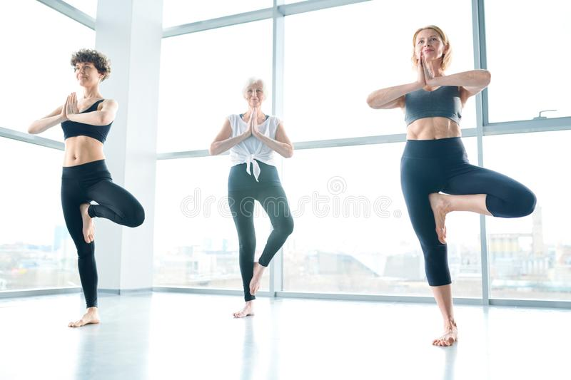 Balancing on the floor. Small group of active sportswomen practicing yoga exercise on right leg with their hands put together by chest royalty free stock photography