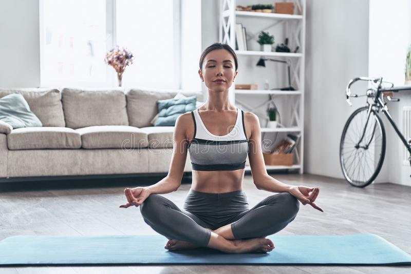 Balancing her mind and body. Beautiful young Asian woman in sports clothing doing yoga while relaxing at home royalty free stock photography