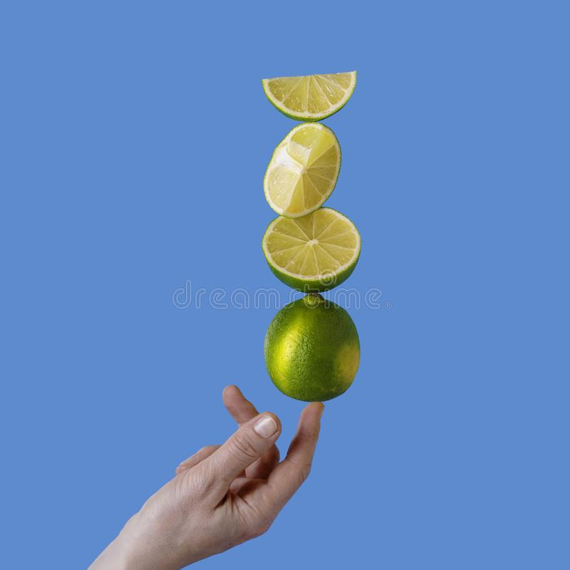 Balancing lime fruits on women finger. Copy space. stock photo