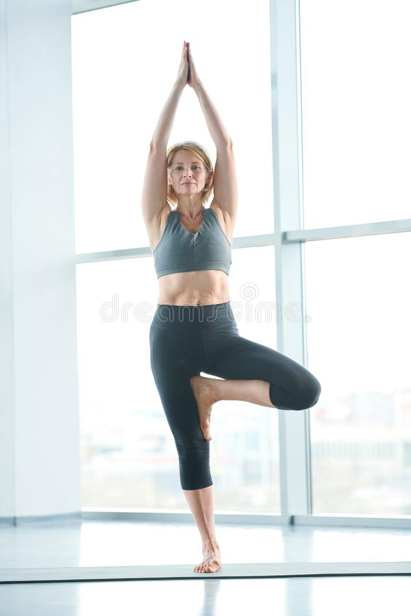 Balancing on one leg. Contemporary mature sportswoman in activewear standing in one of yoga poses with raised arms and one leg bent in knee royalty free stock photo