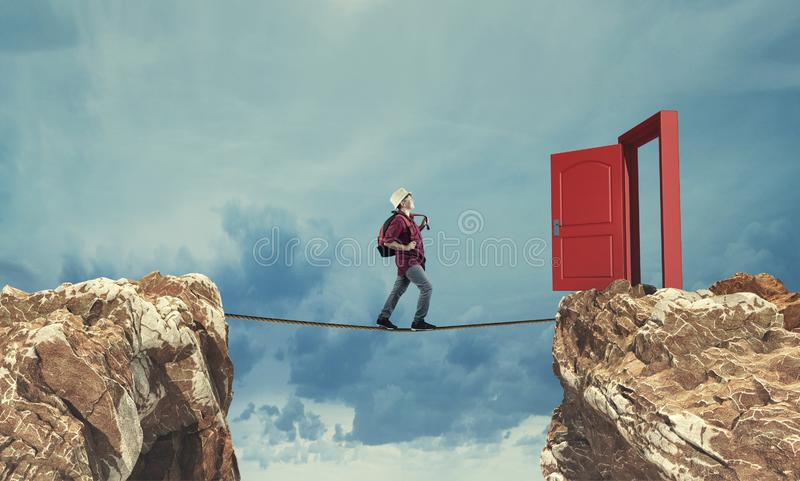 Balancing rope businessman. Surreal challenge overcome . Young man conquering obstacle balancing on slackline rope above a gap  between two mountain peaks.Risk royalty free stock images