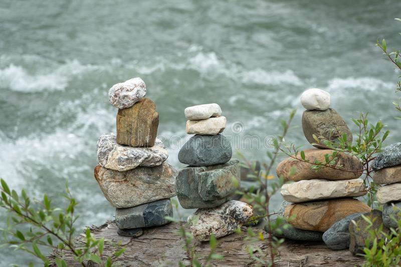 Balancing stones in equilibrium against the backdrop of a mountain river. Balancing stones in equilibrium. Meditation and rest on the bank of the river stock photo