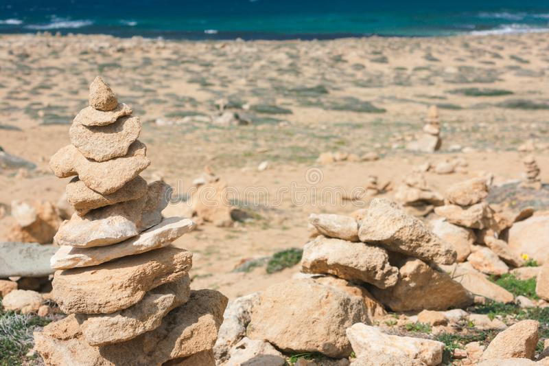 Balans mellan stora stenar på stranden, en mund royaltyfri bild
