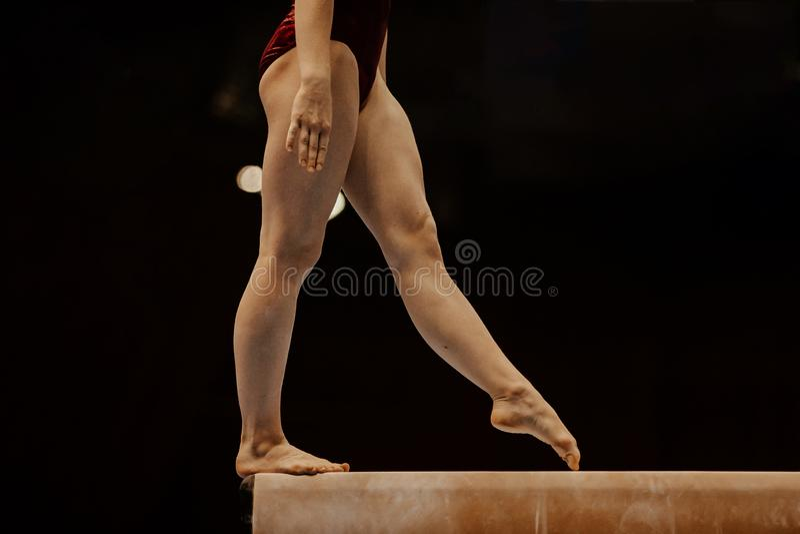 Balansbommen för sidosikten lägger benen på ryggen den kvinnliga gymnasten arkivfoto