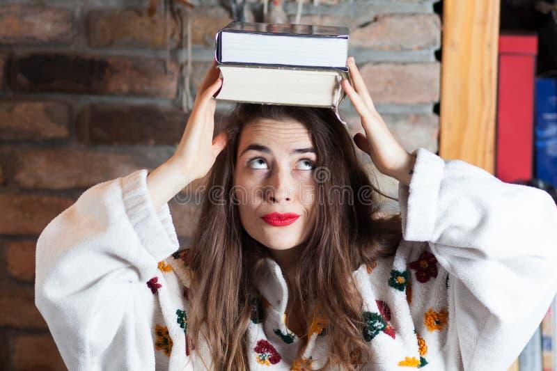 Balansera böcker på hennes huvud royaltyfri foto