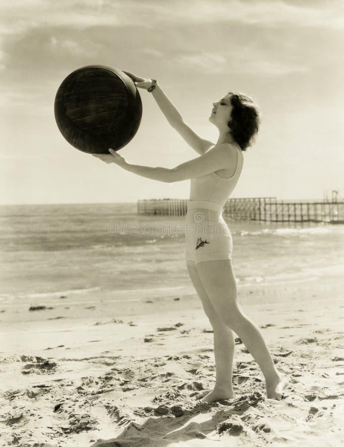 Balansera en medicinboll på stranden arkivbild